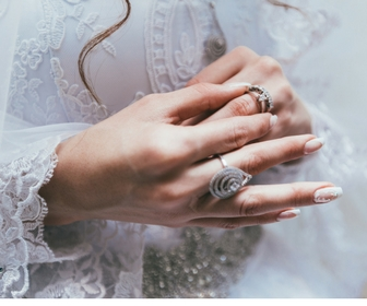 lady's hands with engagement and wedding ring on